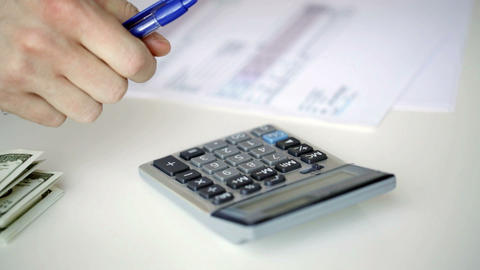 close up of man with calculator counting money Footage