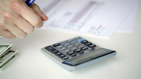 close up of man with calculator counting money Live Action