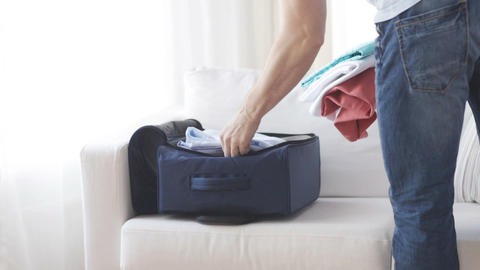 close up of man packing clothes into travel bag Footage