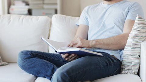 close up of man reading book at home Footage