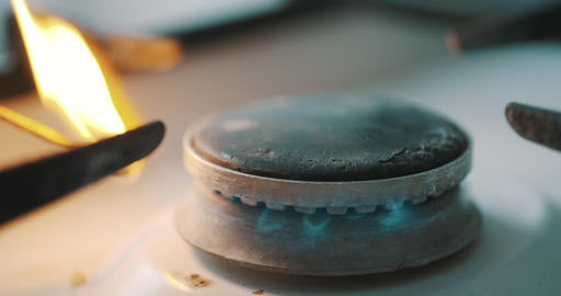 Stove burner igniting into blue cooking flame Footage