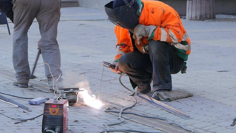 A man with face protection welds metal parts. The welder is working on the Footage