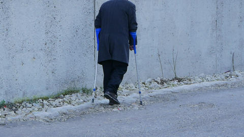 elderly handicapped people background. old man walks in public with crutches Footage