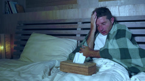 man at home bedroom lying in bed suffering grippe feeling unwell and sick Live Action