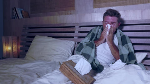 Young man at home bedroom suffering grippe feeling unwell sick sneezing nose Live Action