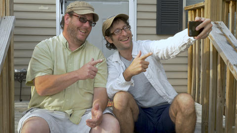 Two happy men sitting on steps in front of a house taking a selfie with a smart Footage