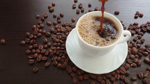Pouring coffee in white cup surrounded by coffee beans on dark background Footage