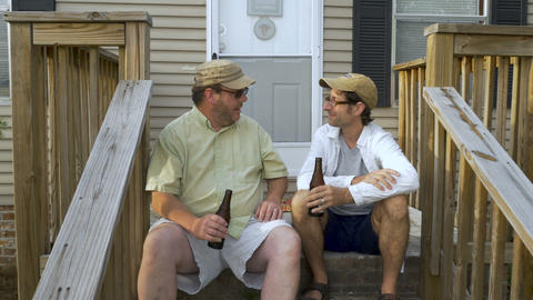 Two men sitting on porch steps talking, holding brown bottles and relaxing - Footage