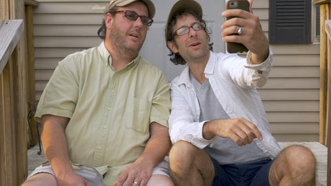Two male best friends taking a selfie photo sitting on porch steps - push in GIF