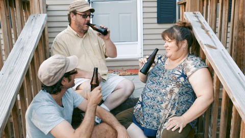Two men and one woman sitting on porch steps cheering with beer bottles and Footage