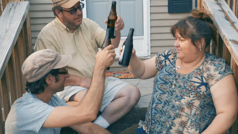 Push in of three friends in their 30s or 40s sitting on porch steps cheering, Footage