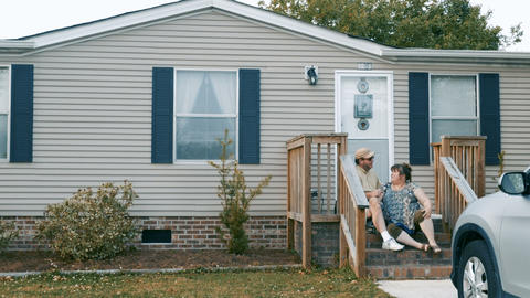 Man and woman sitting on their porch steps of their manufactured home talking Footage