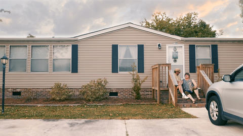 Man and woman couple sitting on porch steps of their manufactured home high five Footage
