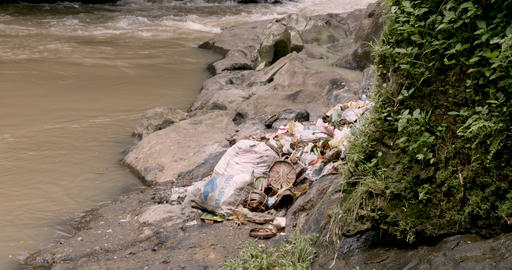 Piles of garbage thrown by the side of a river with leftover offerings in Bali, Footage