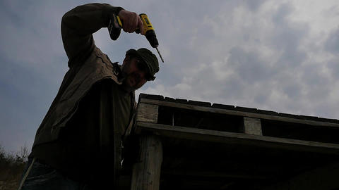 man drilling wooden building against sun slow motion gimbal shot 2 Footage