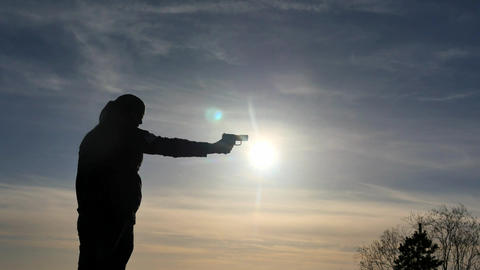 Silhouette of man training to shoot with pistol outdoors ビデオ