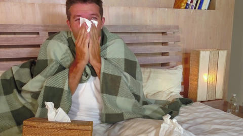 wasted man sick at home in bed covered with blanket sniffing sneezing and Archivo