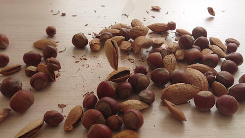 hazelnuts and almonds fall on the table Footage