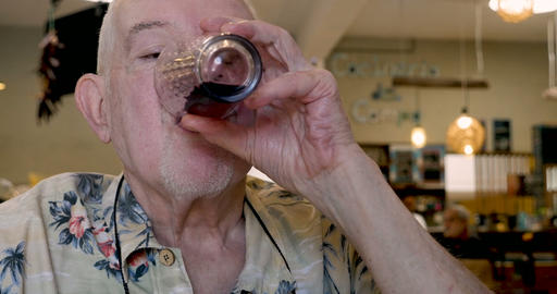 Handsome elderly man in his 70s or early 80s drinking red wine in a cafe while Footage