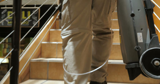 Elderly man carrying a portable oxygen tank with tubes up stairs in a market Footage