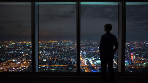 Man looking out a window high above the city Footage
