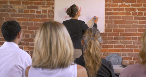 Audience applauding at a business presentation when a woman is writing on white Footage