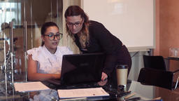 Two young business women discuss a business project in an office using a Footage