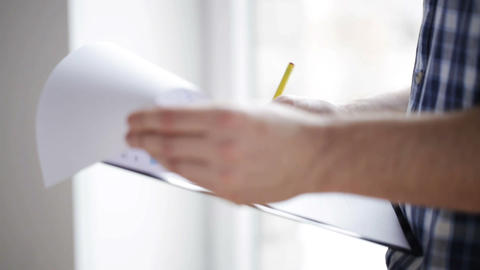 close up of man looking and writing to clipboard Footage
