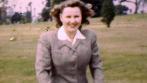 1957: Happy new mother pushes baby stroller in cemetery Footage