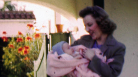1957: Loving mother holds precious bundled newborn baby Live Action