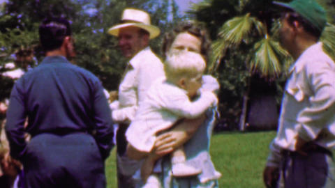 1957: Family outdoor park gathering mother holds blonde child Footage