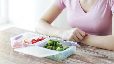 close up of woman eating vegetables from container Footage