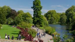 Pan shot of people enjoying the sunshine in St James Park London. Taken on a war Footage