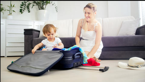 Beautiful young woman packing suitcase with her toddler son Photo