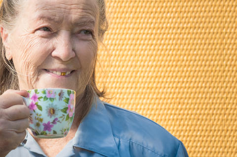 portrait of old grandmother outdoors at sun day. caucasian granny drinking hot フォト