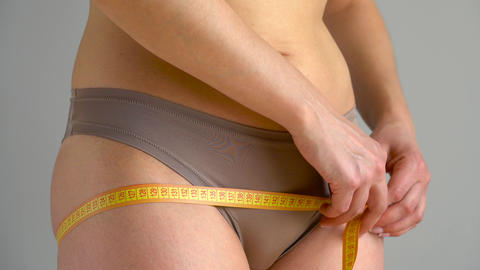 Woman measures her waist, hips and legs with measuring tape Footage