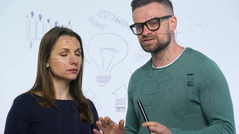 Man and woman discuss the business strategy for success in a modern glass office Footage