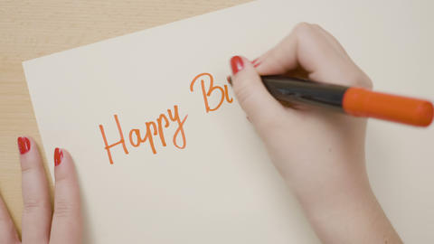Woman hands writing happy birthday on a paper with red marker Footage