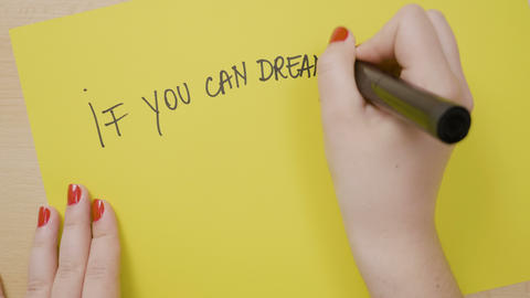 Young girl hands writing if you can dream it you can do it motivational quote on Footage