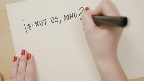 Woman hands writing if not us who and if not now when question marks Footage