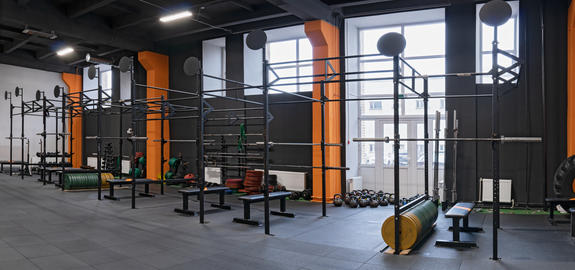 modern interior of the gym for fitness training with horizontal bar and barbells フォト