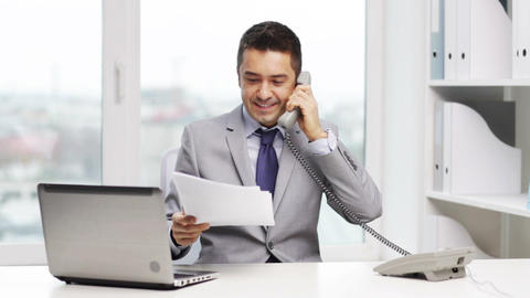 smiling businessman with laptop calling on phone Footage