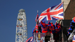 Union Jacks Fly From A Souvenir Stall With The London Eye Rotating In The Backgr stock footage