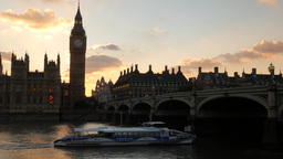 Beautiful sunset behind Parliament in London as a Thames river boat passes under Footage