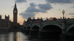 London buses cross Westminster Bridge at Sunset, stopping at Parliament. Shot in Footage