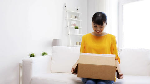 happy asian young woman with parcel box at home Footage