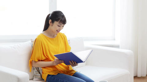 smiling young asian woman reading book at home Footage