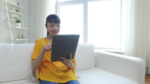happy young asian woman with tablet pc at home Footage