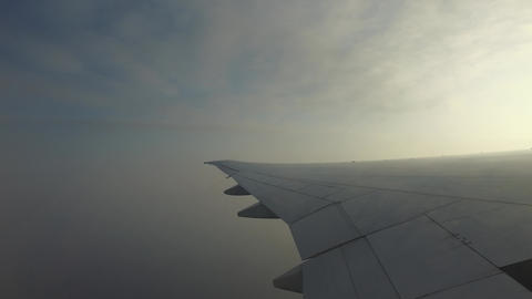 wing of airplane flying in cloudy gray sky Footage