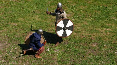 Two Viking warriors fight on swords, one man hit from above and win short duel Footage